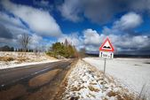 Road  area and warning sign in winter. — Stock fotografie