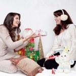 Two beautiful girls giving christmas presents — Stock Photo #33369413