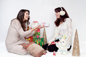 Two beautiful girls giving christmas presents — Foto de Stock