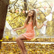 Beautiful woman swinging with autumn leaves — Stock Photo