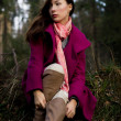 Stock Photo: Well-dressed young womin pink topcoat sitting in forest