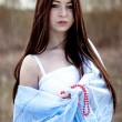 Portrait of a beautiful young woman with long hair in blue fabric — Stock Photo