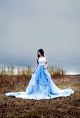 Beautiful young woman with long hair in blue fabric and blue clouds — Stock Photo