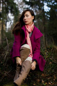 Well-dressed young woman in pink topcoat sitting in forest — Stock Photo