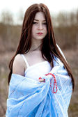 Portrait of a beautiful young woman with long hair in blue fabric — Стоковое фото