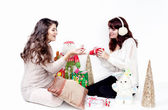 Two smiling women opening christmas presents — Stok fotoğraf