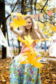 Happy girl throws colorful autumn leaves — Stock Photo