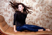 Beautiful girl waving her brown hair on vintage couch — Stock Photo