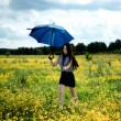 Happy girl running yellow flowers field with blue umbrella — Foto de Stock