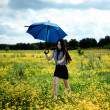 Happy girl running yellow flowers field with blue umbrella — Stock Photo