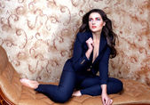 Sexy woman in suit on vintage couch — Stock Photo