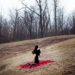 Woman in black dress and long hair sitting on red carpet in cold forest — Stockfoto