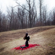 Woman in black dress and long hair sitting on red carpet in cold forest — Foto Stock