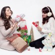 Happy girls opening christmas presents on white background — Stock Photo