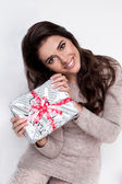 Smiling girl holding a present on white background — Stock Photo