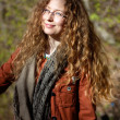 Smiling woman with glasses and blonde curly hair on sunny forest background — Stock Photo