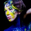 Beauty fashion portrait of woman painted blue and yellow on black background — Stock Photo