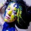 Stock Photo: Beauty fashion portrait of wompainted blue and yellow on black background