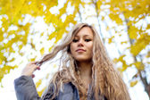 Gorgeous young woman on yellow autumn leaves background — Stok fotoğraf