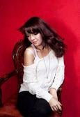 Retrato de belleza de mujer en silla vintage sobre fondo rojo — Foto de Stock