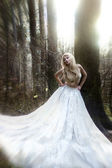 Gorgeous woman in long white skirt in fairytale sunny forest — Stock Photo
