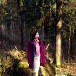 Woman in pink coat in sunshine forest — Stock Photo