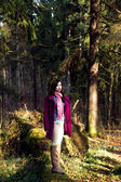 Woman in pink coat in sunshine forest — Stockfoto