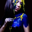 Beauty fashion close up portrait of woman painted blue and yellow with brushes and paint on black background — Stock Photo #36528281