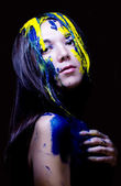 Beauty fashion close up portrait of woman painted blue and yellow on black background — Stock Photo