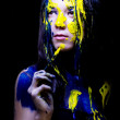 Beauty fashion close up portrait of woman painted blue and yellow with brushes and paint on black background — Stock Photo #36546467
