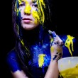 Beauty fashion close up portrait of woman painted blue and yellow with brushes and paint on black background — Stock Photo