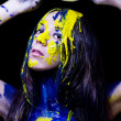 Beauty fashion close up portrait of woman painted blue and yellow with brushes and paint on black background — Stock Photo #36546535