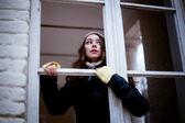 Vrouw op zoek door het raam en uit angst voor iets — Stockfoto