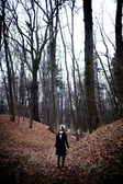 Woman standing in dark cold forest background — Stock Photo