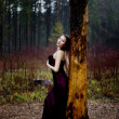 Pale woman in purple dress lying upon a tree — Stock Photo