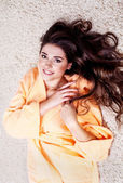 Beautiful woman in orange robe with beautiful brunette hair — Stock Photo