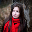 Portrait of woman in red scarf with long brunette hair in cold dark forest — Stock Photo
