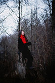 Woman in black coat and red scarf sitting in cold dark forest — Stock Photo