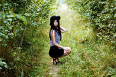 Fashionable woman waving her hair in green forest — Foto Stock