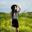 Fashion woman in black hat standing on yellow sunny flowers field — Stock Photo