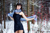 Beautiful woman with bright tinsel in winter forest — Stock Photo