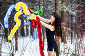 Beautiful woman with bright tinsel in winter forest — ストック写真