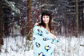Beautiful woman under warm cute wrap in cold snow forest — Stock fotografie