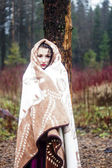 Beautiful woman in warm blanket in forest — Stock Photo