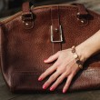 Female hand with bracelet holds a brown leather bag — Stock Photo #43660183