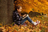Girl playing on the tablet in the park — Stock Photo