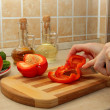 Girl cuts red bell pepper — Stock Photo
