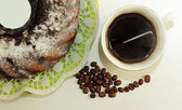 Chocolate cake, a cup of coffee and coffee beans — Stock Photo