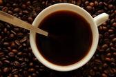 Une tasse de café, café en grains et une cuillère à café, vue de dessus — Photo