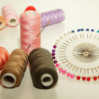 Colorful spools of thread, a needle to inject into a coil and a set of pins — Stock Photo
